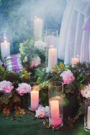 Arrangement of flowers, candles and green plants
