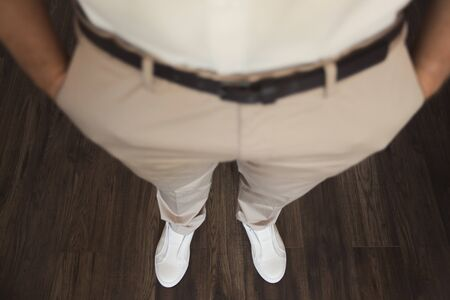 Man corrects belt, fees groom, mans hands, dressing, man buttons pants, jeans.