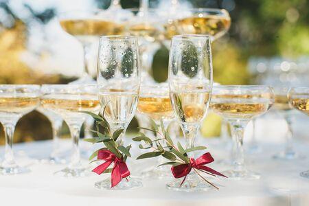 Schöner Hügel mit Champagner beim Bankett für das Brautpaar. Brille der Braut und des Bräutigams.