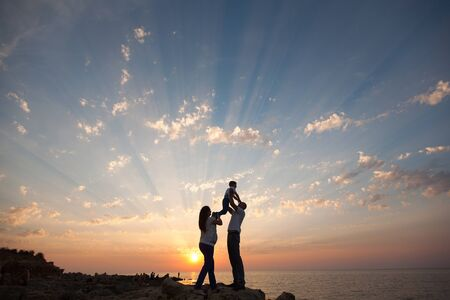 Pregnancy and happy family. The pregnant wife with her husband and child holding hands walking on the sea sunset. Archivio Fotografico