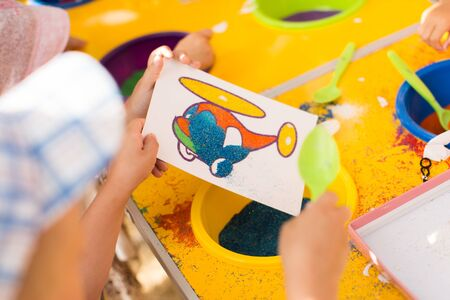 A child draws with colored sand picture. Cartoon characters. 免版税图像