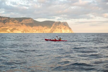Kayaks. Canoeing in the sea near the island with mountains. People kayaking in the ocean.
