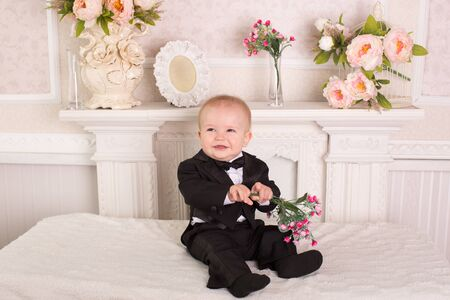 Child in a tuxedo sitting on the bed next to the fireplace with flowers in their hands. Stock Photo