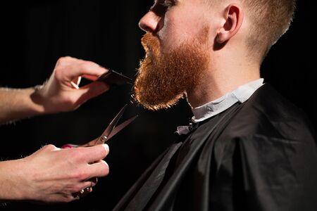 Meister schneidet Haare und Bart im Barbershop. Friseur macht Frisur mit einer Schere und einem Metallkamm Standard-Bild