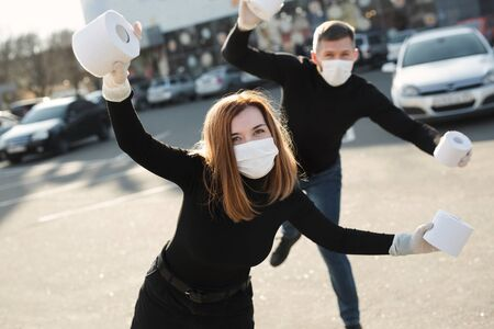 A woman and a man in a coronavirus face mask hold large rolls of toilet paper on a city street and indulge Stock Photo