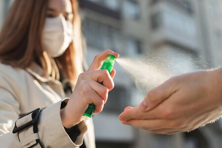 People who use alcohol-based antiseptic gel and wear a preventive mask prevent infection with the Covid-19 coronavirus outbreak, a woman washes a mans hands with hand sanitizer