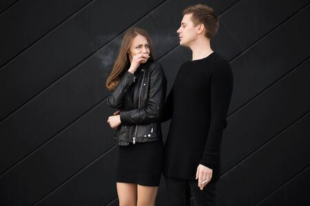 Passive smoking concept. Woman is covering her face from cigarette smoke. Not Smoking woman asks her man to quit Smoking