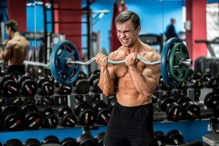 Very power athletic guy standing workout in the gym. Archivio Fotografico