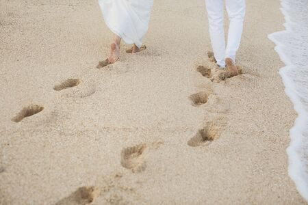 The bride and groom walk hand in the sand. footprints in the sand near the ocean.