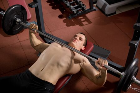 Brutal athletic man pumping up muscles on bench press. Stock fotó
