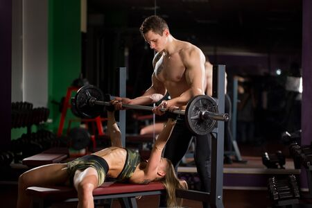 Sport, fitness, teamwork, bodybuilding and people concept - young woman and personal trainer with barbell flexing muscles in gym. 写真素材
