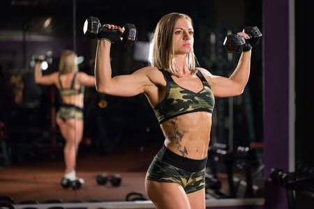 Beautiful bodybuilder woman with lifting dumbbells. Sporty girl showing her well trained body. Well-developed muscles by strength training.