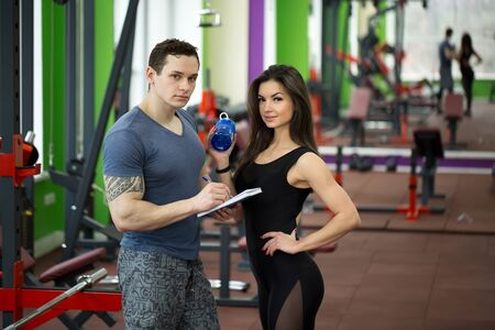 Handsome muscled male trainer consulting attractive young female in gym, both smiling. Archivio Fotografico
