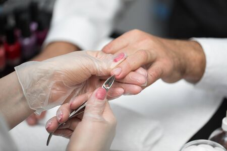 Close-up Of A Manicurist Cutting Off The Cuticle From The Person's Fingers Imagens