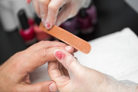 Girl manicurist doing manicure for man in beauty salon.