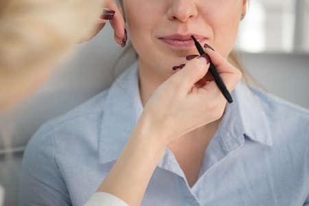 Makeup in salon. Stylist paints faces. Lips.