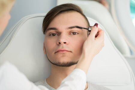 Professional Make-up artist doing young man makeup in studio.