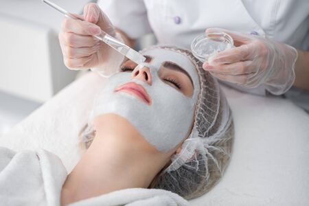 Face peeling mask, spa beauty treatment, skincare. Woman getting facial care by beautician at spa salon.