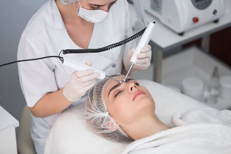 Macro close up portrait of woman having cosmetic galvanic beauty treatment in spa.Therapist applying low frequency current with electrodes on face Standard-Bild