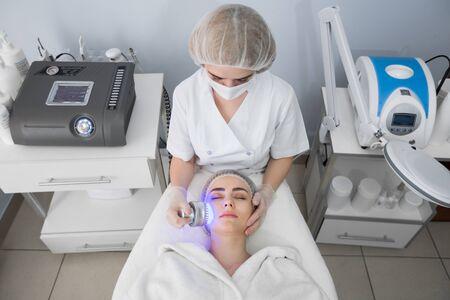 Ultrasonic massager. Light skin treatment, the woman in the beauty salon.