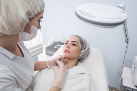 Hands of cosmetologist making injection in face, lips. Young woman gets beauty facial injections in salon. Face aging, rejuvenation and hydration procedures. Aesthetic cosmetology Stock fotó