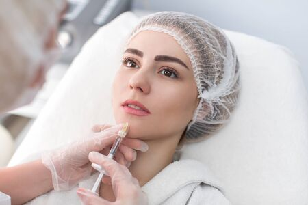 Hands of cosmetologist making injection in face, lips. Young woman gets beauty facial injections in salon. Face aging, rejuvenation and hydration procedures. Aesthetic cosmetology