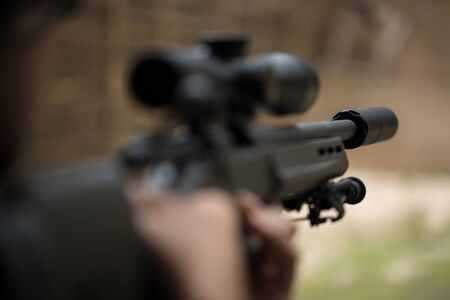 Sniper shooting rifle by looking through a scope