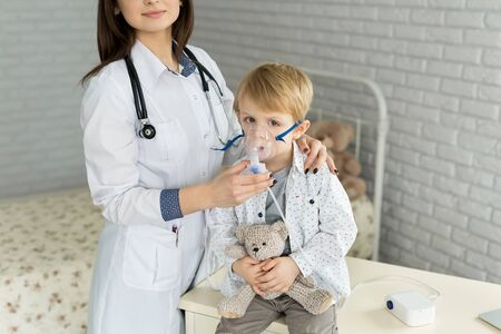 Medical doctor applying medicine inhalation treatment on a little boy with asthma inhalation therapy by the mask of inhaler.