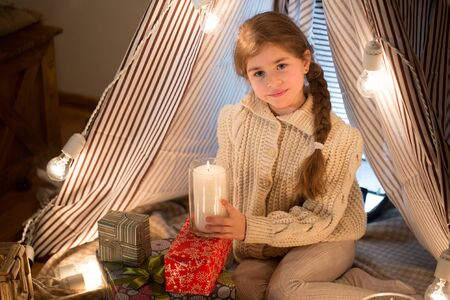 Beautiful little girl sitting with a burning candle in his hands. Christmas. New year. Studio