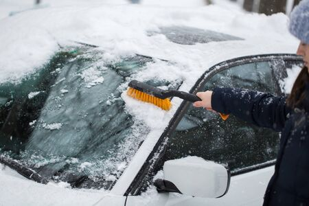 Beautiful woman removing snow from car windshield
