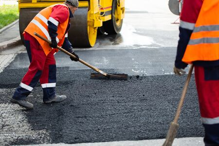 The road workers' working group updates part of the road with fresh hot asphalt and smoothes it for repair