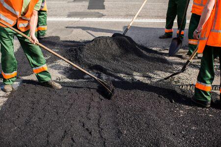Workers on Asphalting paver machine during Road street repairing works. Street resurfacing. Fresh asphalt construction. Bad road
