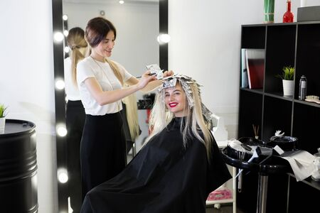 Blonde woman dying her hair at the beauty salon.