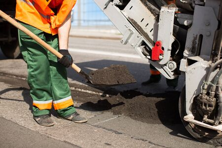 Road workers repair work. work sleeps shovel the material into the machine