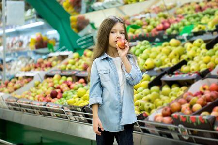 Petite fille choisissant une pomme bio dans un magasin.