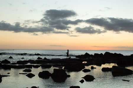 A fisherman is fishing in the black stones in the ocean