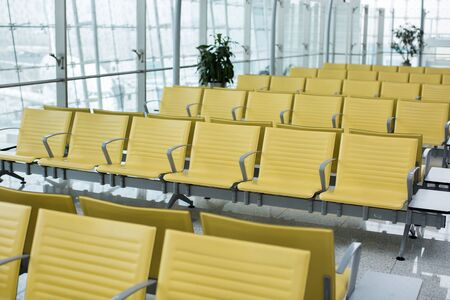 Bench in the terminal of airport. empty airport terminal waiting area with chairs.