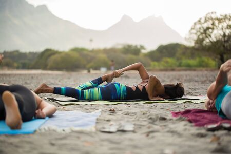Women doing yoga exercises or supported pigeon pose on the background mountain on the empty beach of the Indian ocean in Mauritius