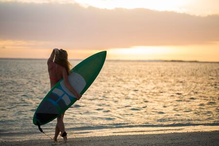 Surfing surfer girl looking at ocean beach sunset. Silhouette of female bikini woman looking at water with standing with surfboard having fun living healthy active lifestyle. Water sports with model. 免版税图像