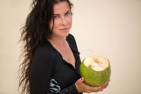 Portrait of a young woman with a coconut in her hands on the beach. Standard-Bild