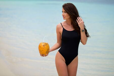 Young woman in black swimsuit with coconut cocktail on the beach.