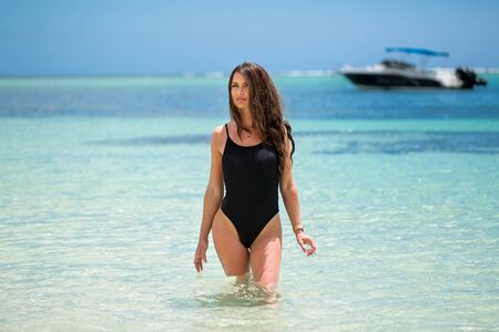 Young pretty hot sexy woman on the tropic island in summer near the sea and blue sky having fun.