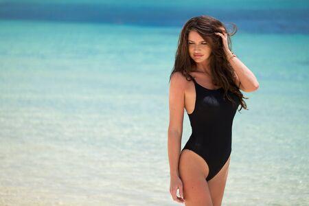 Beautiful young woman in sexy bikini standing at sea beach.