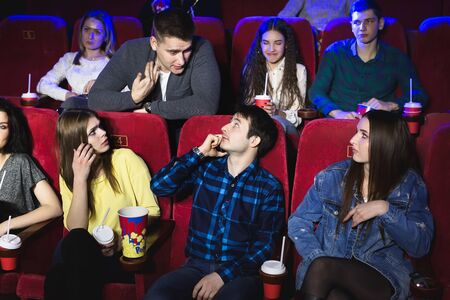 A man is talking loudly on the phone in a movie theater and prevents you from watching a movie. The man makes a remark and asks to turn off the phone