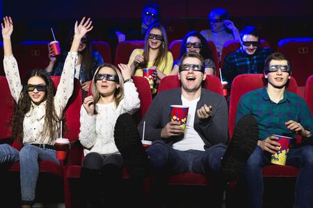 Friends in the cinema watch a funny movie with 3D glasses, laugh, have fun
