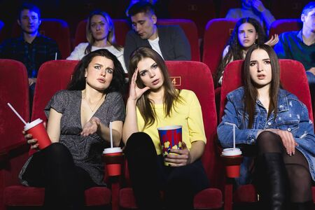 Girls watching a really boring movie at the cinema theater. Bad film. Archivio Fotografico