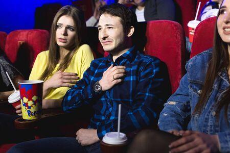 Amigos, un hombre y una mujer están viendo una película en un cine llorando