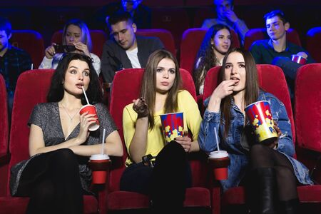 Girls watching a really boring movie at the cinema theater. Bad film.