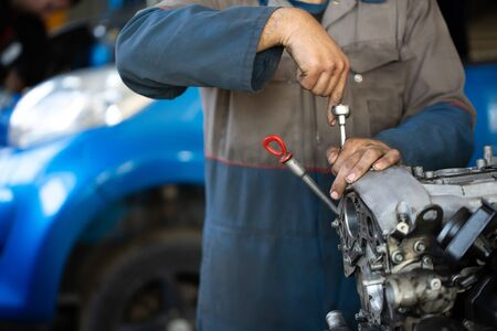 An auto mechanic repairs an internal combustion engine.