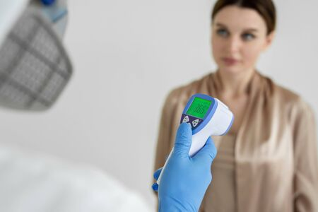 Infectious disease doctor measures the temperature of a woman patient with an infrared thermometer in a clinic during coronavirus epidemic. Covid-19